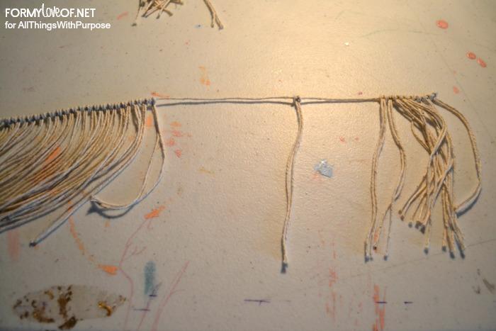 larks head knot the smaller strings onto the longer string