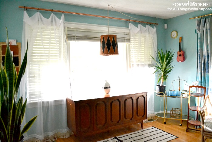 sheer sequin and fringe accented curtains flank credenza