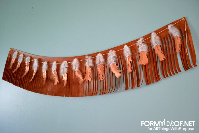 blue-grey wall with leather fringe and copper dipped overlapping banners