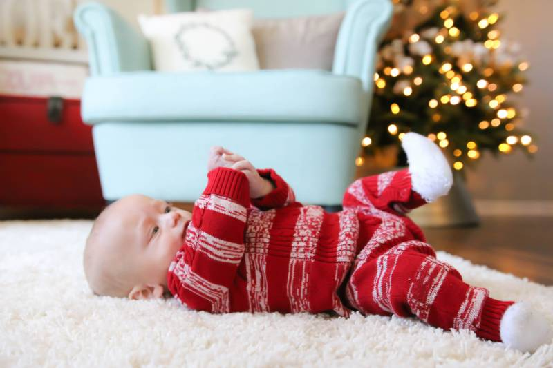 baby in Christmas pajamas playing with hand